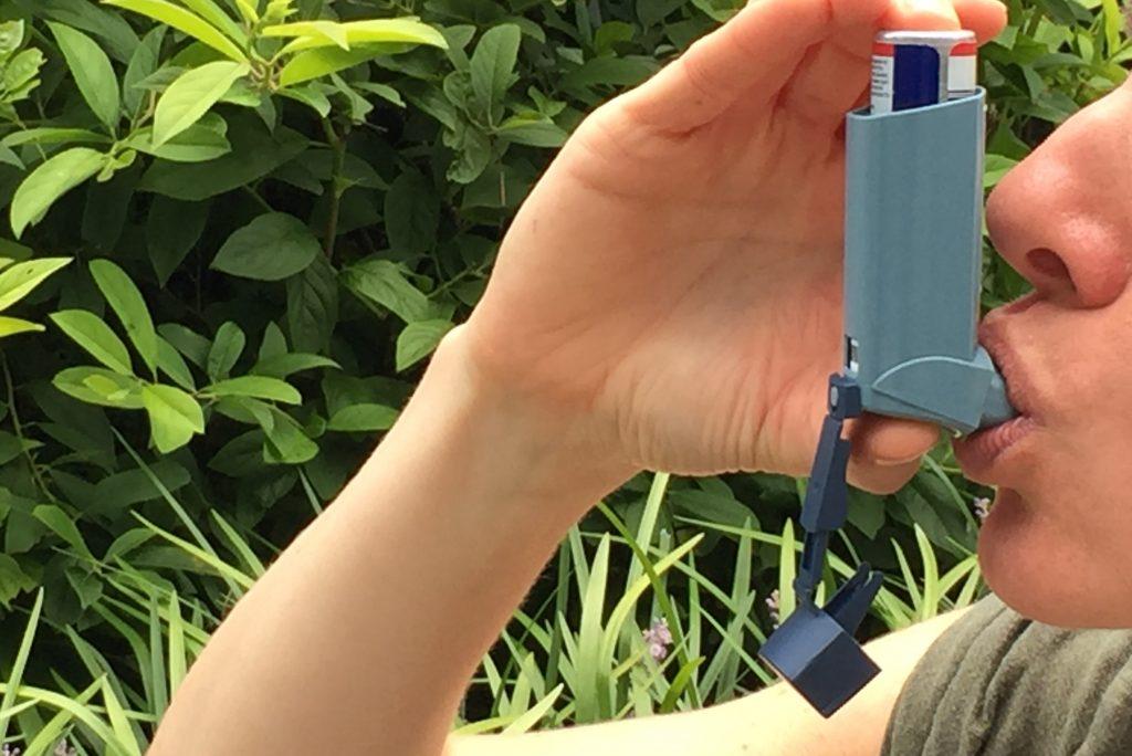 Person inhaling on an asthma ventilator