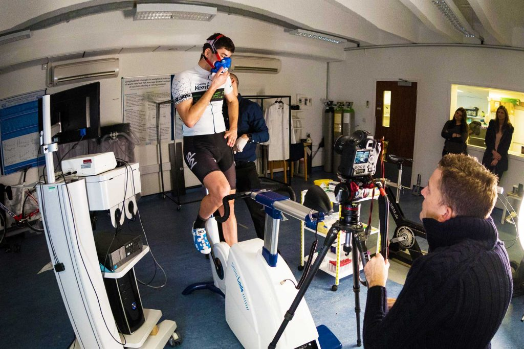 A man on an exercise bike wearing a plastic mask while being monitored on camera