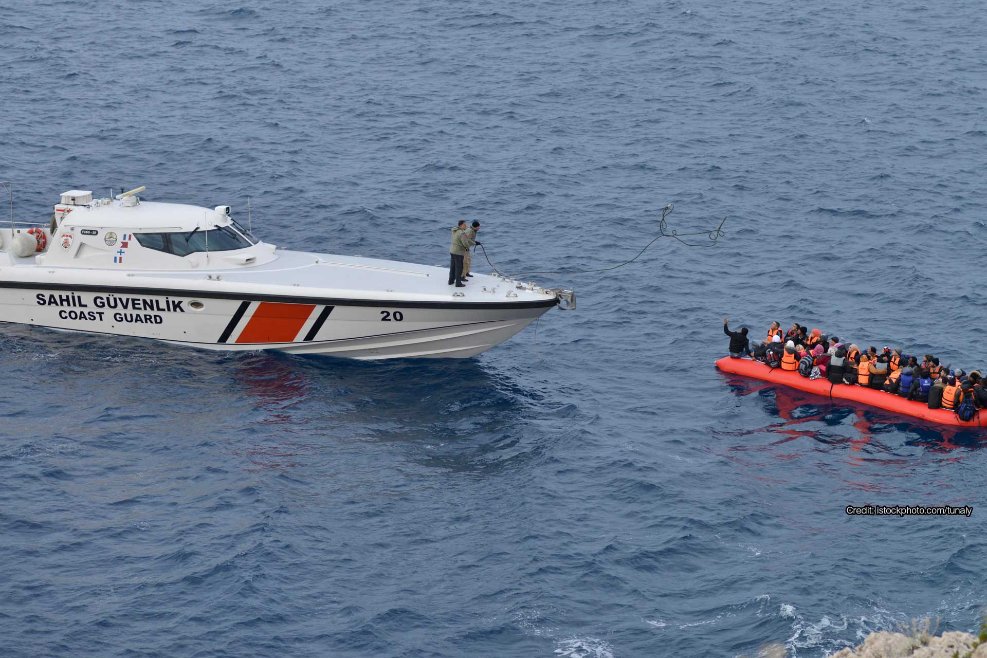 Refugees in boat being thrown a line by a coast guard boat