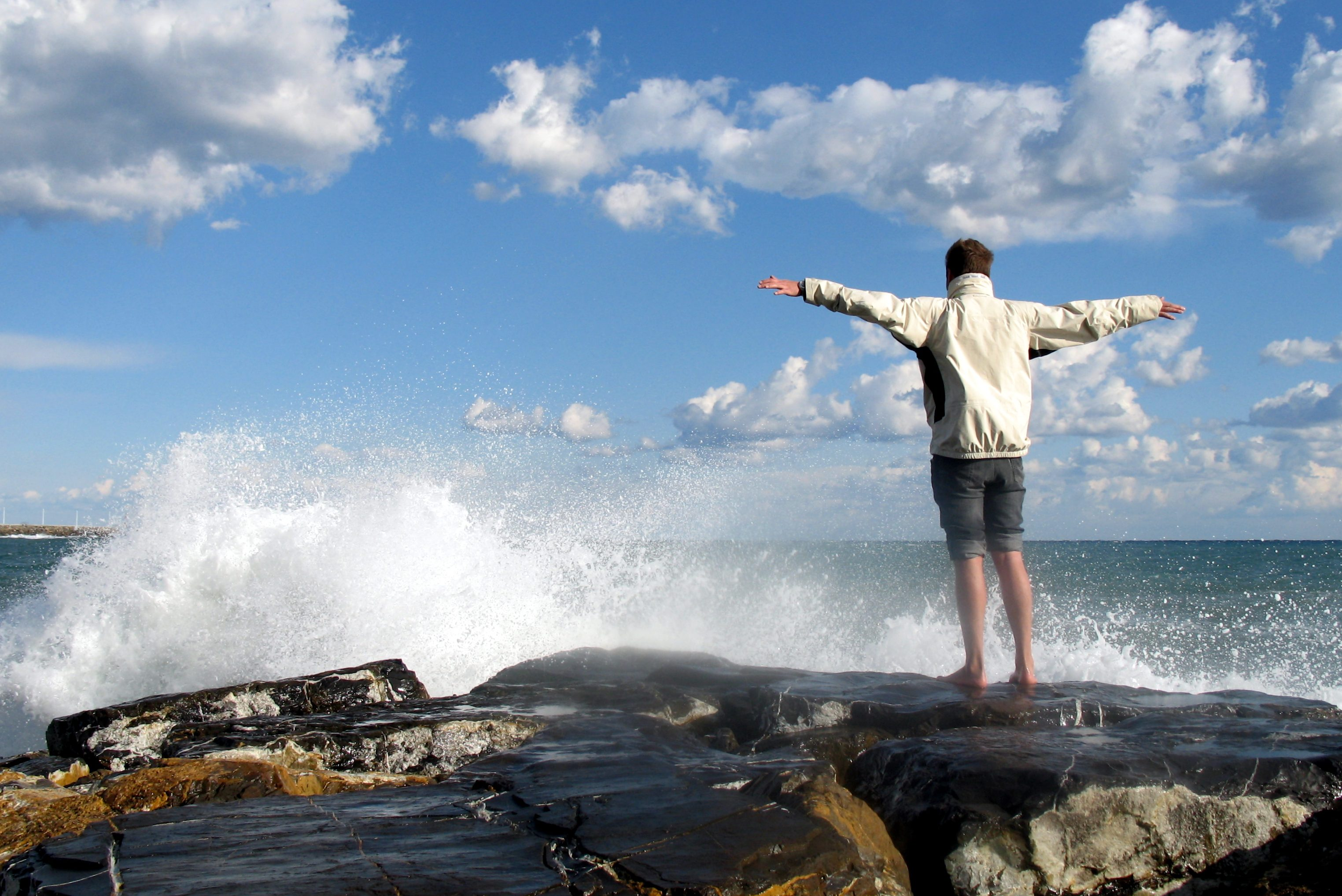 Man standing in front of breaking waves holding out arms