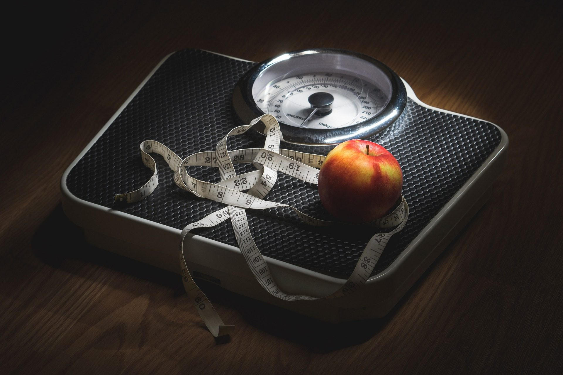 Weighing scales, an apple and a tape measure
