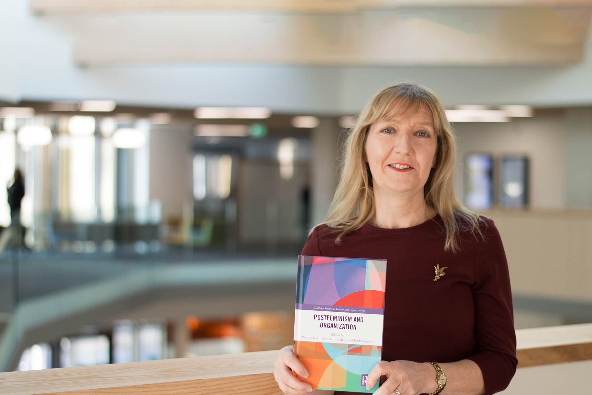 Dr Patricia Lewis in the Sibson building holding a book she published