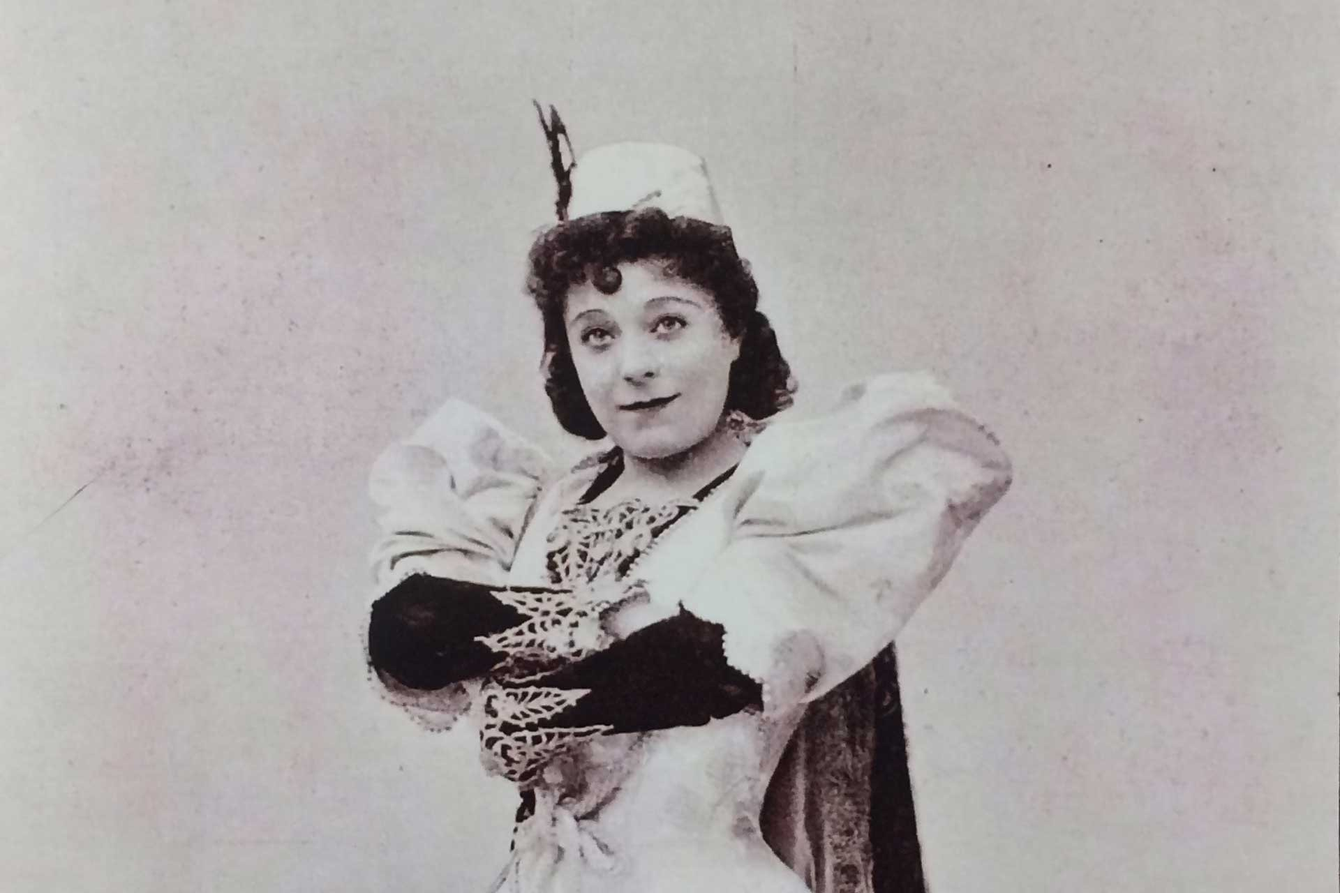 Victorian lady dressed up in a pantomime outfit with folded arms and a wry look on her face